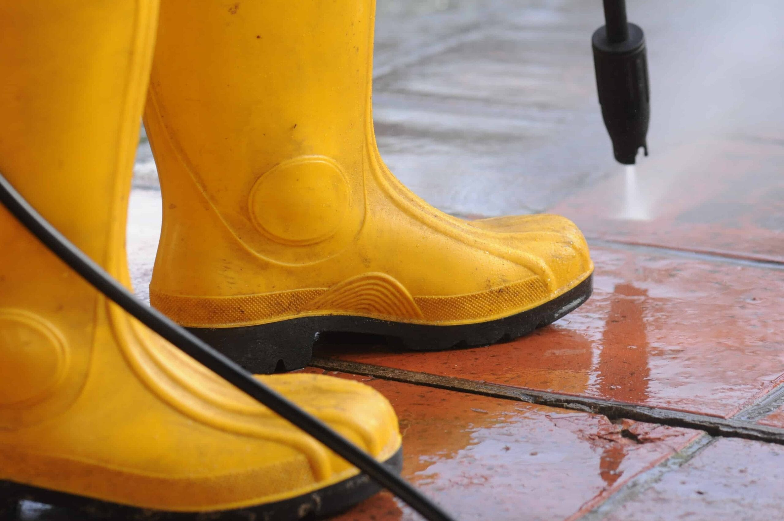 person wearing yellow rubber boots with high pressure water nozzle cleaning dirt tiles scaled
